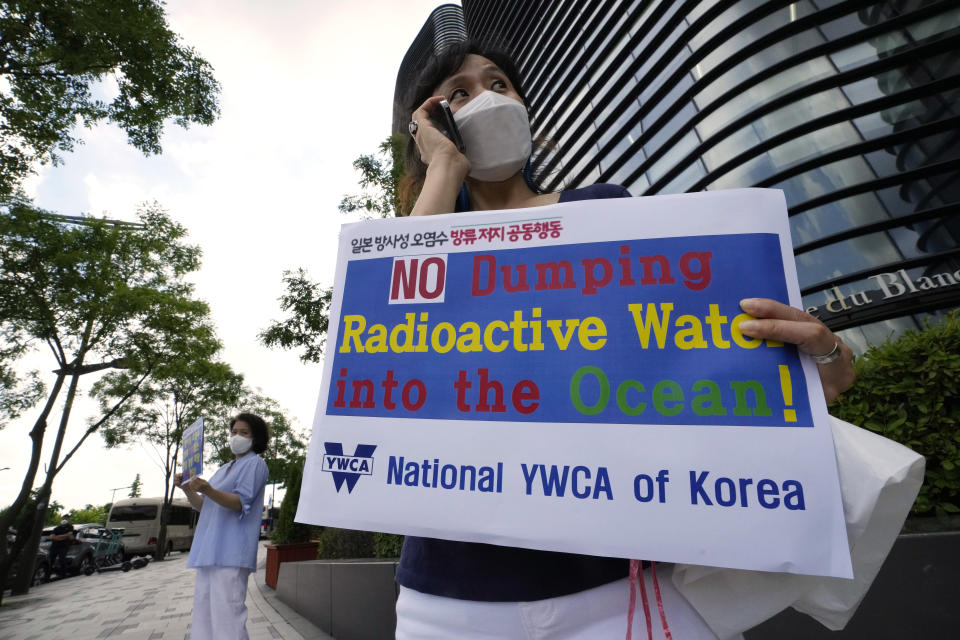 Members of the National YWCA of Korea stand to oppose South Korean President Moon Jae-in's possible visit to Japan, in front of a building which houses Japanese embassy in Seoul, South Korea, Monday, July 19, 2021. Moon has decided not to visit Japan for the Tokyo Summer Olympics, citing a failure to set up a summit with Japan's prime minister that would produce meaningful results in improving relations.(AP Photo/Ahn Young-joon)