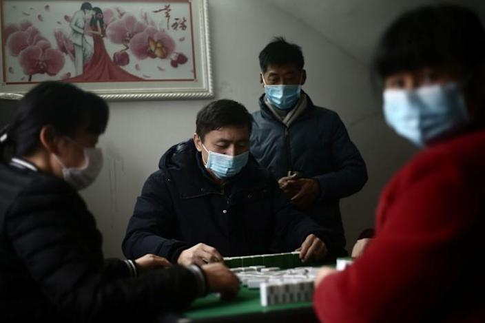 People wearing face masks play mahjong during home quarantine on the first day of the Chinese Lunar New Year of the Rat, at a village in Hubei