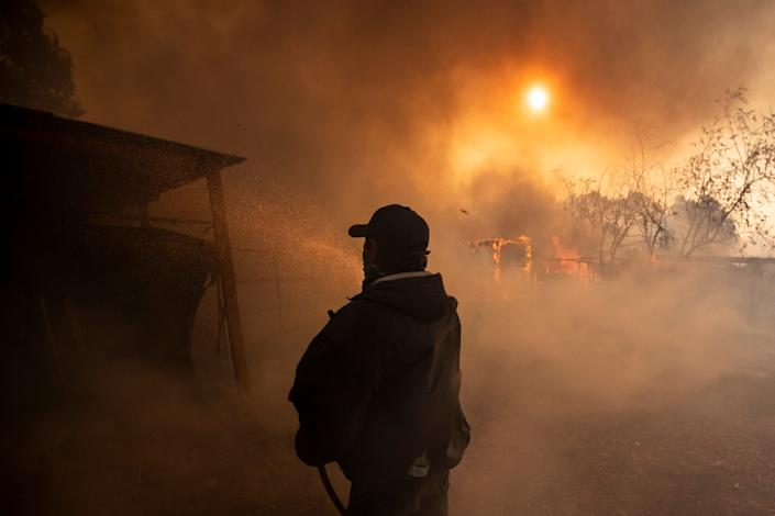 A rancher tries to put out a fire in a henhouse in a burning ranch as the Easy Fire spreads near Simi Valley, North of Los Angeles, Calif., on Oct. 30, 2019. (Photo: Etienne Laurent/EPA-EFE/Shutterstock)