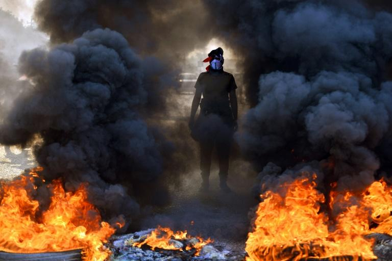 An Iraqi protester stands before burning tyres at a roadblock in the central holy shrine city of Najaf