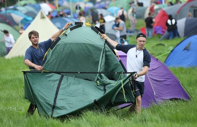 Men carry a tent on the first day of Glastonbury Festival at Worthy Farm, Somerset