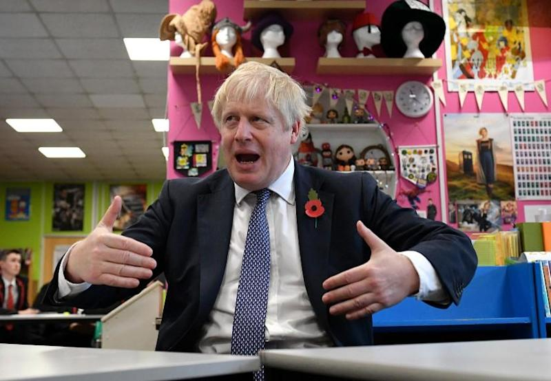 Boris Johnson gestures as he talks with teachers - but not sixh formers - during visit to George Spencer Academy in Stapleford, Nottinghamshire: Getty