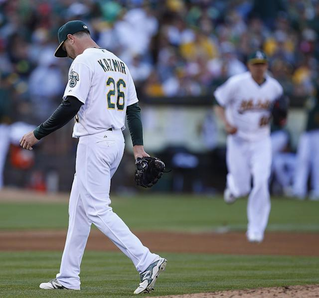Oakland Athletics' pitcher Jesse Chavez, right, comes into the game as Oakland Athletics starting pitcher Scott Kazmir (26) was taken out of the game against the Los Angeles Angels in the fourth inning of a baseball game Sunday, Aug. 24, 2014, in Oakland, Calif. (AP Photo/Tony Avelar)