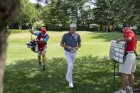 Kramer Hickok, center, walks up to the sixth tee during the second round of the Travelers Championship golf tournament at TPC River Highlands, Friday, June 25, 2021, in Cromwell, Conn. (AP Photo/John Minchillo)