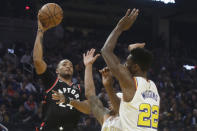 Toronto Raptors guard Norman Powell, left, shoots against Golden State Warriors guard Andrew Wiggins (22) and guard Damion Lee during the first half of an NBA basketball game in San Francisco, Thursday, March 5, 2020. (AP Photo/Jeff Chiu)