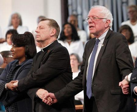 "Dr. Bernice King, (L-R), Rev. Michael Louis Pfleger and Senator Bernie Sanders lock arms as they sing ""We Shall Overcome"" during the Martin Luther King Jr. Commemorative Service at Ebenezer Baptist Church in Atlanta, Georgia, U.S. January 16, 2017. REUTERS/Tami Chappell"