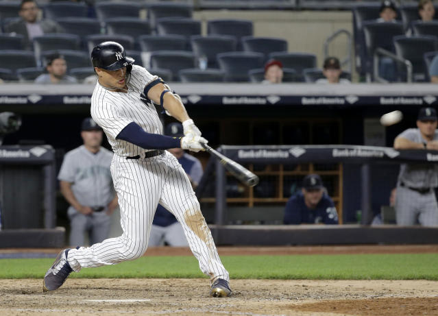 New York Yankees' Giancarlo Stanton hits a walk-off two-run home run during the ninth inning of a baseball game against the Seattle Mariners at Yankee Stadium Wednesday, June 20, 2018, in New York. The Yankees defeated the Mariners 7-5. (AP Photo/Seth Wenig)