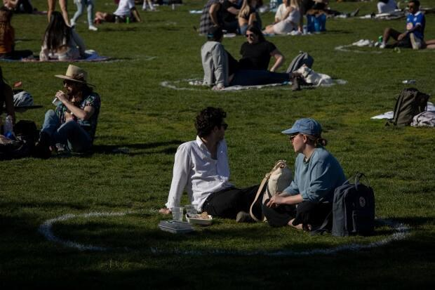 Toronto residents enjoy warm weather while sitting in freshly-painted physical distancing circles at Trinity Bellwoods Park in Toronto on May 13, 2021. (Evan Mitsui/CBC - image credit)