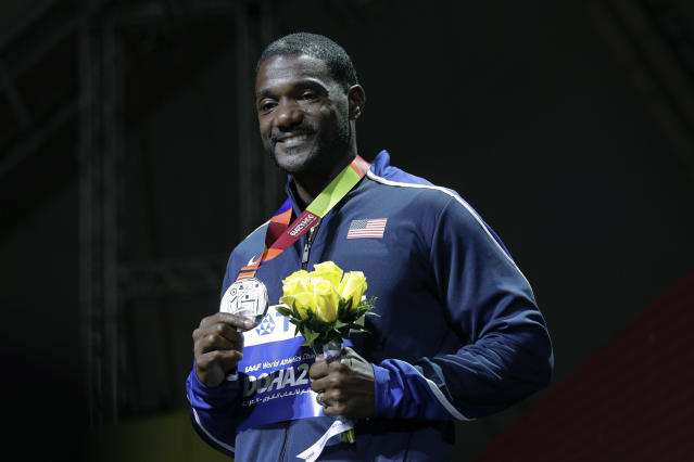 FILE - In this Sept. 29, 2019, file photo, silver medal winner Justin Gatlin, of the United States, smiles during the medal ceremony for the men's 100m event at the World Athletics Championships in Doha, Qatar. Gatlin and Jamaican Asafa Powell may be late 30-something sprinters but they feel as youthful as ever. There's no retirement talk even with the Tokyo Games delayed for a year due to the coronavirus. (AP Photo/Nariman El-Mofty, File)