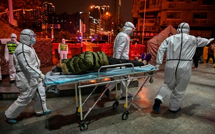 Medical staff members wearing protective clothing to help stop the spread of a deadly virus which began in the city, arrive with a patient at the Wuhan Red Cross Hospital in Wuhan on January 25, 2020 - HECTOR RETAMAL/AFP via Getty Images