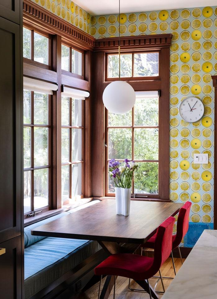 Fornasetti's Arance Lemon wallpaper adds a burst of color to the breakfast nook, which is crowned by a globe pendant by Pablo Lighting.