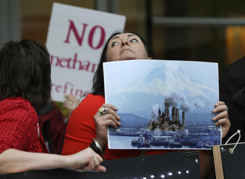 FILE - In this Feb. 10, 2016, file photo, Francesca Siena holds a photo of Mount Rainier and the Port of Tacoma that has been computer modified to include the image of a refinery as she protests in Tacoma, Wash., outside a public meeting to gather opinion on a proposed methanol plant that would be built at the Port of Tacoma. A new federal lawsuit filed Tuesday, Nov. 12, 2019, aims to kill plans to build one of the world's biggest methanol refineries along the Columbia River. (AP Photo/Ted S. Warren, File)