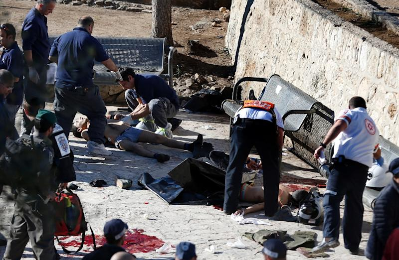 Israeli police officers and emergency personnel inspect the bodies of two of the reported Palestinian assailants killed following an attack at Damascus Gate, a main entrance to Jerusalem's Old City on February 3, 2016 (AFP Photo/Ahmad Gharabli)