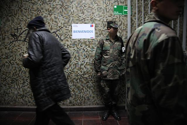 In this May 24, 2013 photo, soldiers guard the entrance of a homeless shelter at the indoor stadium Estadio Victor Jara as people enter for the evening in Santiago, Chile. The stadium, which opened its doors on May 15 as a temporary shelter to house people throughout the winter who normally sleep on the streets, is where Chilean folk singer Victor Jara was tortured and killed in 1973, just days after Chile's bloody 1973 military coup. Today the stadium is named after him. (AP Photo/Brittany Peterson)