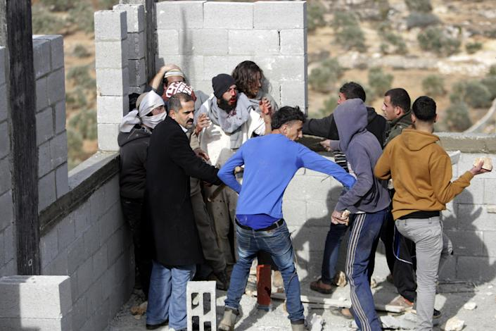 """FILE - In this file photo taken Tuesday, Jan. 7, 2014, some Palestinians try to keep others from further injuring Israeli settlers who are being detained by Palestinian villagers in a building under construction near the West Bank village of Qusra, southeast of Nablus. The annual rate of Israeli settler attacks against Palestinians has almost quadrupled in eight years, U.N. figures show, buttressing claims that Israeli security forces have largely failed to stem the so-called """"price tag"""" campaign in which thugs cut down trees, deface mosques and beat Palestinian farmers. (AP Photo/Nasser Ishtayeh, File)"""