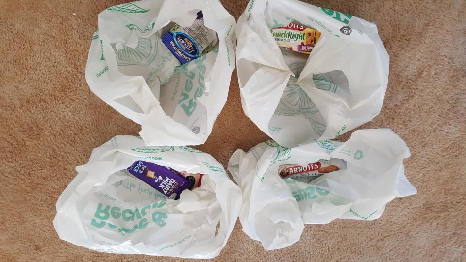 Photo shows four Woolworths plastic shopping bags with single items inside.