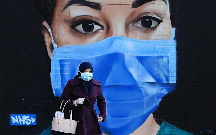A woman wearing a face mask walks past a piece of street art depicting an NHS worker - Getty