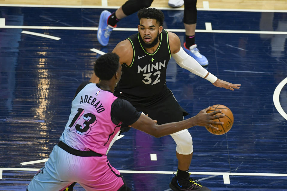 Miami Heat center Bam Adebayo (13) tries to get past Minnesota Timberwolves center Karl-Anthony Towns (32) during the first half of an NBA basketball game Friday, April 16, 2021, in Minneapolis. (AP Photo/Craig Lassig)