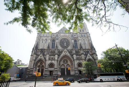 FILE PHOTO:    People drive past the Cathedral of St. John the Divine in New York, June 25, 2013.  REUTERS/Carlo Allegri/File Photo