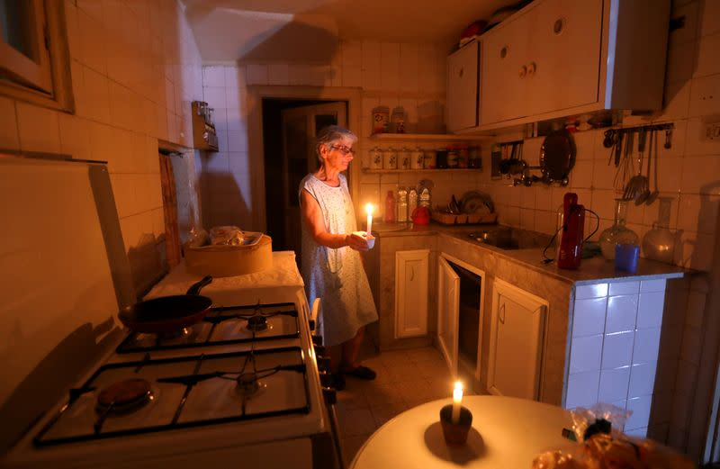 FILE PHOTO: Samira Hanna,70, walks in her kitchen as she holds a candle due to a power cut, in Beirut