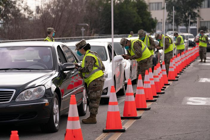 Members of the National Guard help motorists check in at a federally-run COVID-19 vaccination site set up on the campus of California State University of Los Angeles in mid-February.
