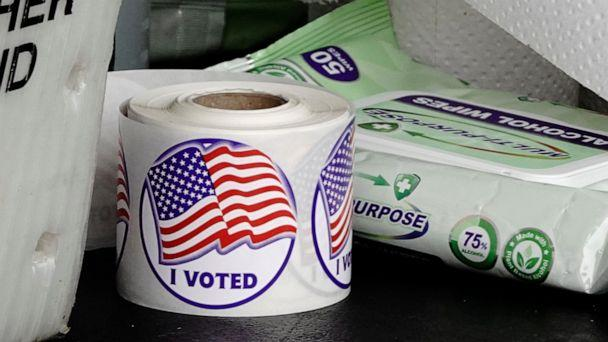 PHOTO: A roll of 'I Voted' stickers is seen next to a packet of alcohol wipes at a drive-thru early voting site in the City Hall parking lot in Eau Claire, Wis., Oct. 23, 2020.  (Bing Guan/Reuters)