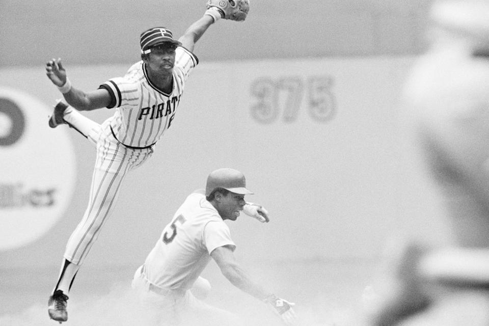 FILE - Pittsburgh Pirates second baseman Rennie Stennett leaps to try and avoid New York Mets' Steve Henderson sliding in trying to break up a double play during the fourth inning of a baseball game in Pittsburgh, in this Aug. 14, 1977, file photo. Stennett completed the double play to first base. Rennie Stennett has died. He was 72. The team, citing information provided by the Stennett family, said Stennett passed away early Tuesday morning, May 18, 2021, following a bout with cancer. (AP Photo/File)