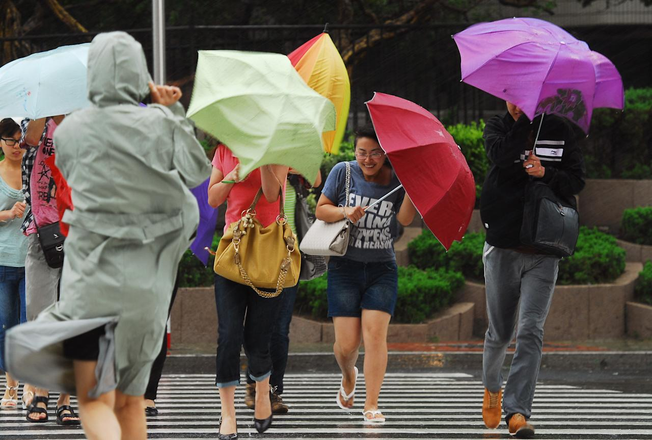 In this photo provided by China's Xinhua News Agency, people walk against wind as a fierce storm brought by Typhoon Muifa hits Yantai, a coastal city in east China's Shandong Province, Monday, Aug. 8, 2011. The tropical storm was lashing northeast China and North Korea as it approached land Monday, but fears of a toxic chemical spill appeared to have eased after a breached dike guarding a chemical plant was reinforced. (AP Photo/Xinhua, Chu Yang) NO SALES