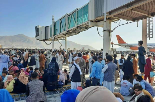 Afghans crowd onto the tarmac of the Kabul airport on Aug. 16, 2021, to flee the country as the Taliban takes control of Afghanistan. (AFP/Getty Images - image credit)