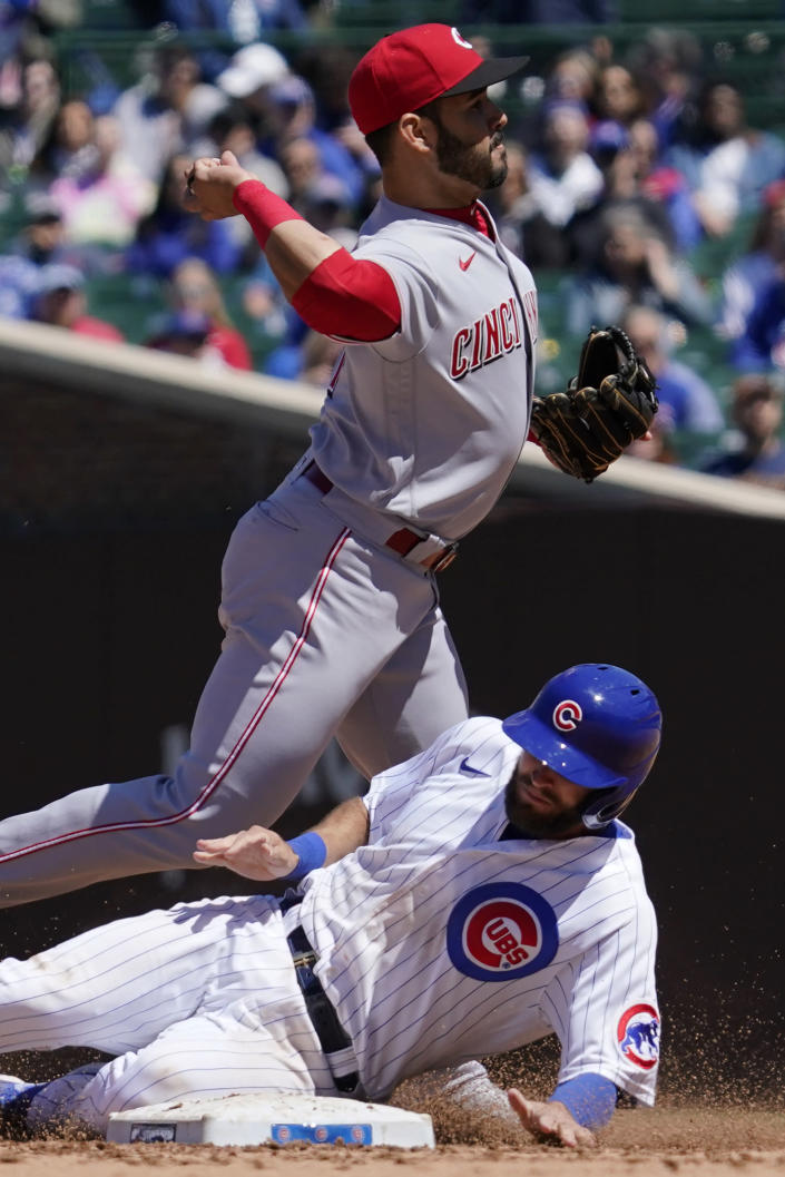 Cincinnati Reds shortstop Eugenio Suarez, top, throws out Chicago Cubs' Eric Sogard at first after forcing out David Bote during the fourth inning of a baseball game in Chicago, Saturday, May 29, 2021. (AP Photo/Nam Y. Huh)