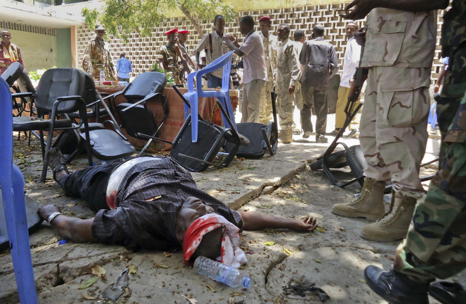 A man wounded in the blast lies on the ground at the Somali National Theater in Mogadishu, Somalia Wednesday, April 4, 2012. An explosion Wednesday at a ceremony at Somalia's national theater killed at least 10 people including two top sports officials in an attack by an Islamist group on a site that symbolized the city's attempt to rise from two decades of war. (AP Photo/Farah Abdi Warsameh)
