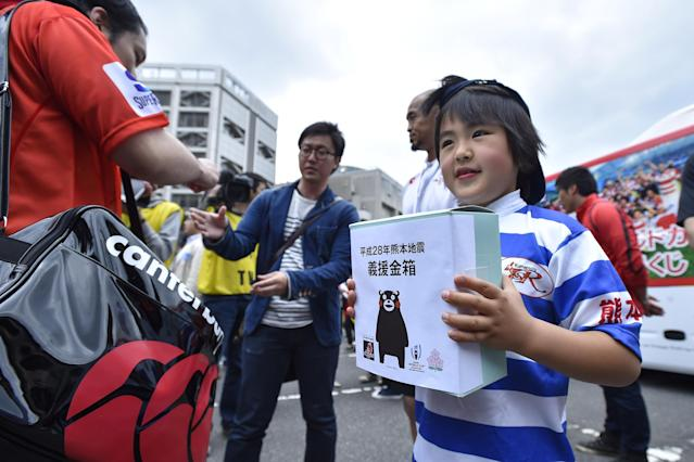 TOKYO, JAPAN - APRIL 23: A child asks for donations of support for the victims of the earthquake in Kumamoto during the round nine Super Rugby match between the Sunwolves and the Jauares at Prince Chichibu Memorial Ground on April 23, 2016 in Tokyo, Japan. (Photo by Koki Nagahama/Getty Images)