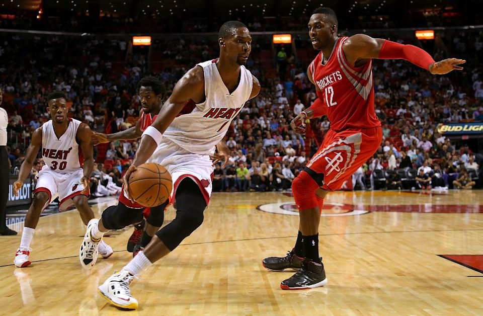 Chris Bosh (L) of the Miami Heat drives past Dwight Howard of the Houston Rockets, during their NBA game at American Airlines Arena in Miami, Florida, on November 4, 2014 (AFP Photo/Mike Ehrmann)