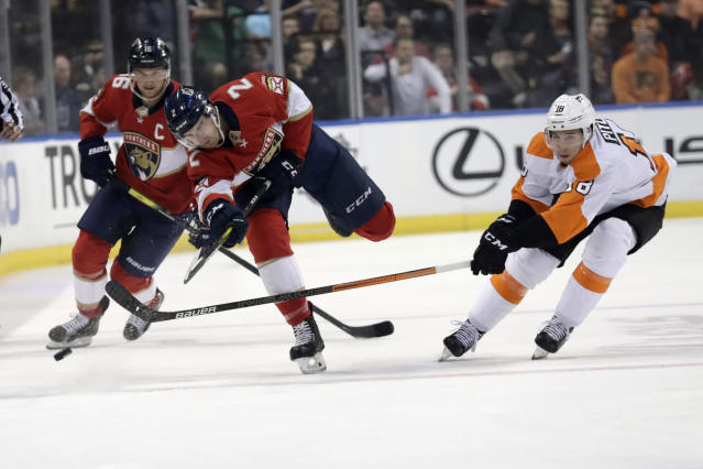 Florida Panthers defenseman Josh Brown (2) passes the puck as Philadelphia Flyers center Tyler Pitlick (18) defends during the first period of an NHL hockey game Thursday, Feb. 13, 2020, in Sunrise, Fla. (AP Photo/Lynne Sladky)