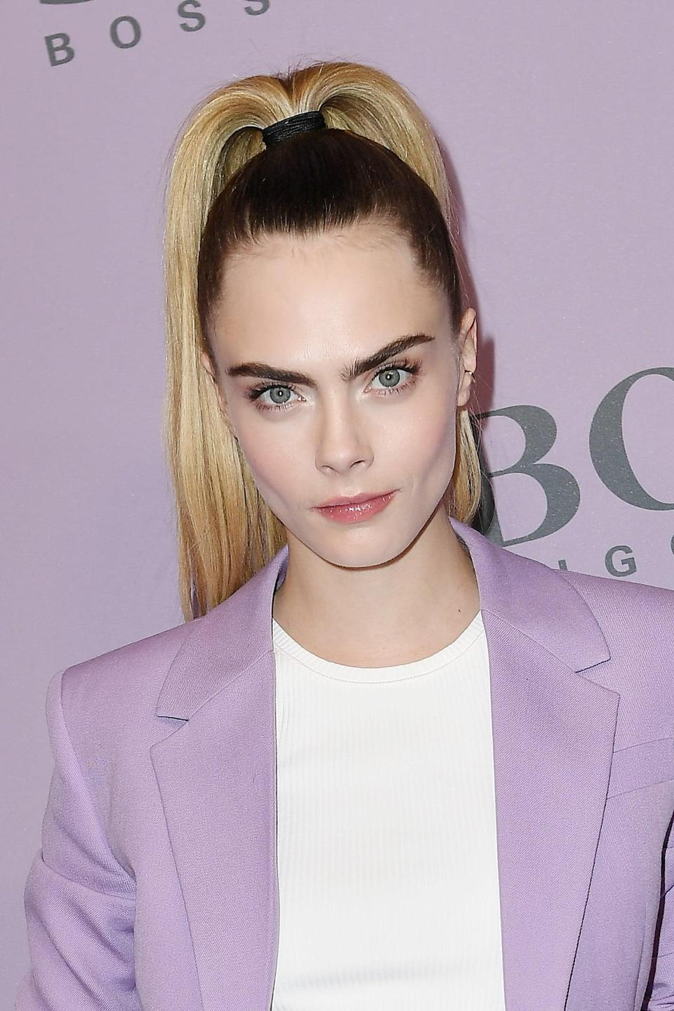 <p>Sometimes you just can't beat a simple high ponytail. Whilst in Milan in February for Fashion Week, Delevingne chose to wear a superhigh blond ponytail to contrast her dark brunette roots and pretty lilac suit. </p>