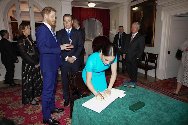 The Duke and Duchess of Sussex sign the book at the awards. (Press Association)