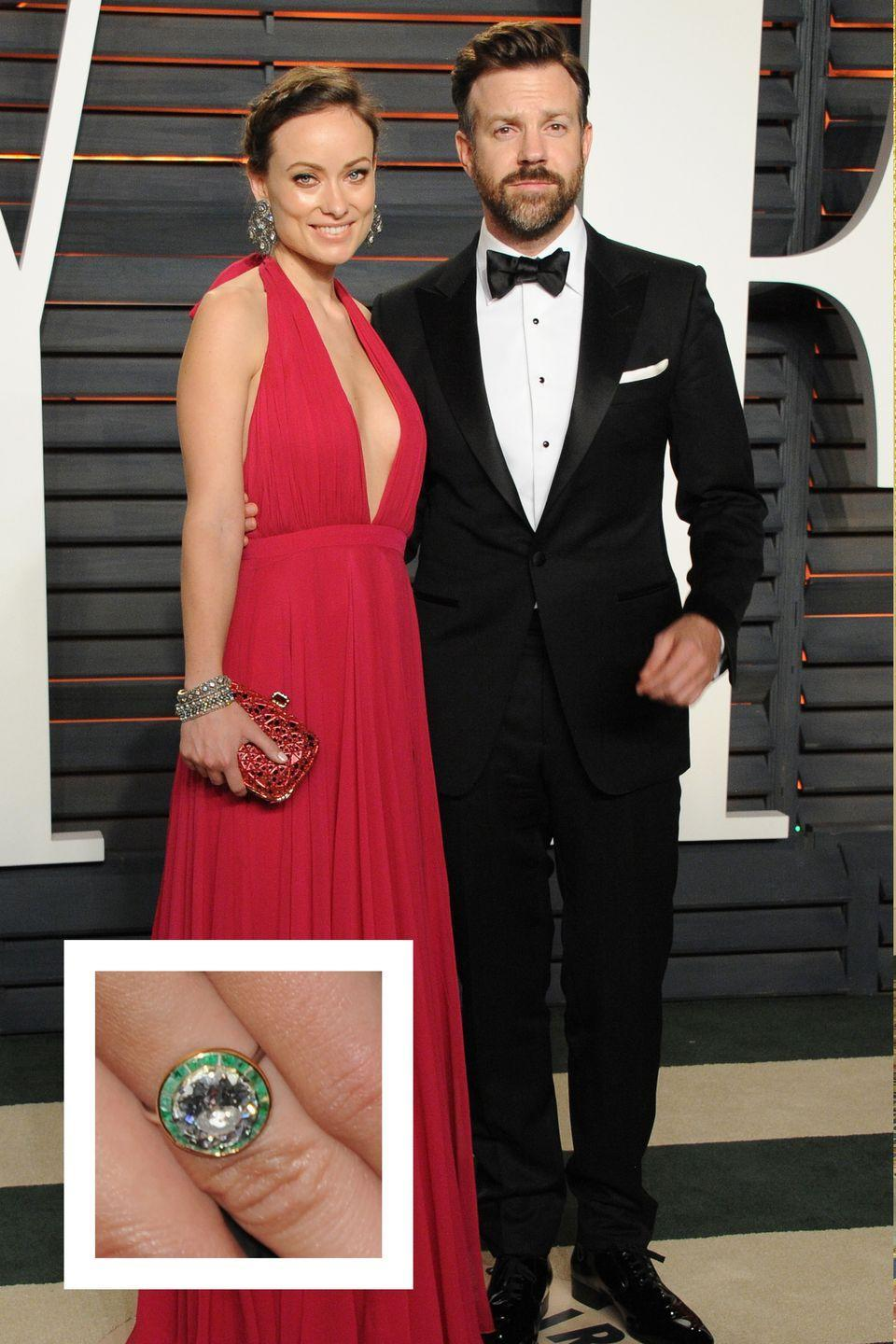 """<p>Olivia Wilde and longtime boyfriend Jason Sudeikis announced their engagement in January 2013. Wilde's dazzling engagement ring features a gorgeous round diamond surrounded <a href=""""https://www.townandcountrymag.com/the-scene/weddings/news/g1616/emerald-engagement-rings/"""" rel=""""nofollow noopener"""" target=""""_blank"""" data-ylk=""""slk:by an emerald halo"""" class=""""link rapid-noclick-resp"""">by an emerald halo</a> on a thin yellow gold band. </p>"""