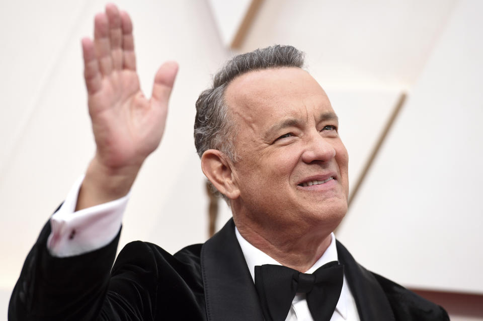 """FILE - In this Sunday, Feb. 9, 2020 file photo, Tom Hanks arrives at the Oscars at the Dolby Theatre in Los Angeles. On Friday, May 15, 2020, The Associated Press reported on videos circulating online incorrectly asserting actor Tom Hanks and Chicago Mayor Lori Lightfoot support the """"New World Order,"""" a conspiracy theory built on the idea that the world's most wealthy and powerful are plotting to overthrow democracy and install a single, global authoritarian government. The clip featuring Hanks was taken from a five-minute video of him addressing the class of 2020 at Wright State University. (Photo by Jordan Strauss/Invision/AP)"""