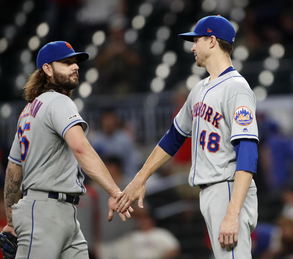 New York Mets starting pitcher Jacob deGrom (48) and relief pitcher Robert Gsellman (65) celebrate after defeating the Atlanta Braves in 10-2 in a baseball game Tuesday, June 18, 2019, in Atlanta. (AP Photo/John Bazemore)