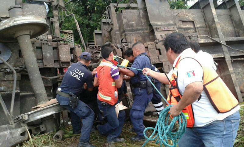 """In this photo release by the Civil Protection of the State of Tabasco, police agents and rescue workers work at a site where a train derailed in Tabasco, Mexico, Sunday, Aug. 25, 2013. An cargo train known as """"The Beast,"""" carrying at least 250 Central American migrants heading to the U.S. derailed in a remote region of southern Mexico on Sunday, killing five and injuring 16, authorities said. (AP Photo/Civil Protection of the State of Tabasco)"""