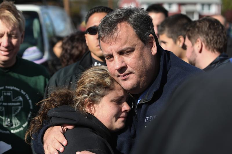 FILE - In this Nov. 3, 2012 file photo, New Jersey Gov. Chris Christie comforts Kerri Berean in Little Ferry, N.J., after Superstorm Sandy caused a tidal surge on the Hackensack River that overtook a natural berm protecting the town. For Christie, leadership after Sandy often came with an empathetic hug. For New York Gov. Andrew Cuomo, it came with an angry tirade at utilities slow to restore power. For New York City Mayor Michael Bloomberg, it came with cool, businesslike assurance. (AP Photo/The Star-Ledger, David Gard, Pool, File)