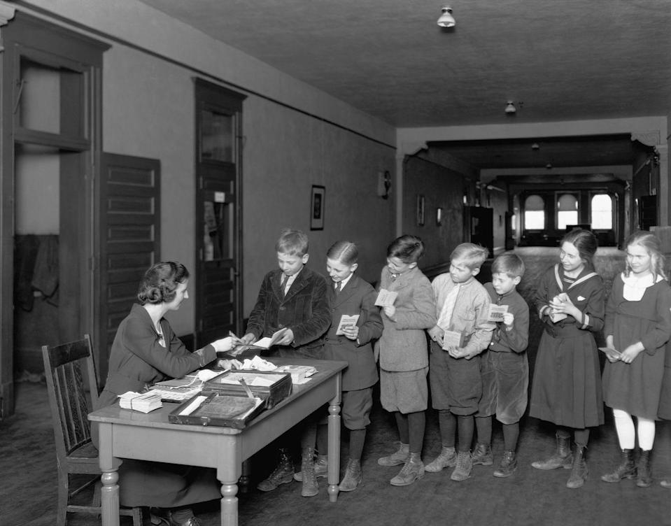 <p>A group of schoolchildren line up in an orderly fashion at their teacher's desk.</p>