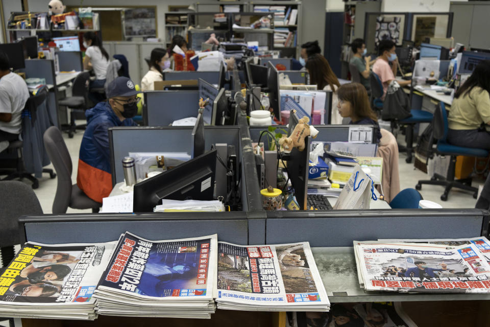 """Reporters work at the news room of Apple Daily Monday, April 26, 2021, in Hong Kong. A year ago, the pro-democracy Apple Daily newspaper published a front-page headline saying Hong Kong's governing principle of """"one country, two systems is dead."""" On Thursday, June 17, 2021, the newspaper was facing its greatest peril. Three top editors and two senior executives were arrested under Hong Kong's new national security law. (AP Photo/Vincent Yu)"""