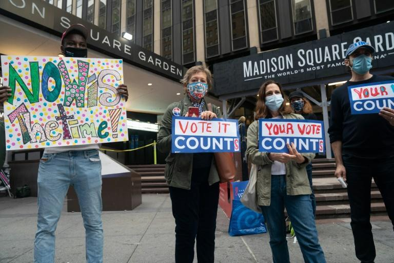 Activists hold up signs outside Madison Square Garden in New York on October 24, 2020
