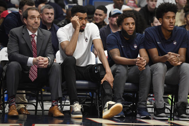 Connecticut's Tyler Polley, second from left, watches play from the bench in the first half of an NCAA college basketball game, Sunday, Jan. 12, 2020, in Hartford, Conn. Polley is out for the season after he tore his left ACL at practice on Friday. (AP Photo/Jessica Hill)