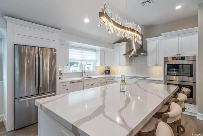 the kitchen at a house for sale in long island with marble countertops and white cabinets