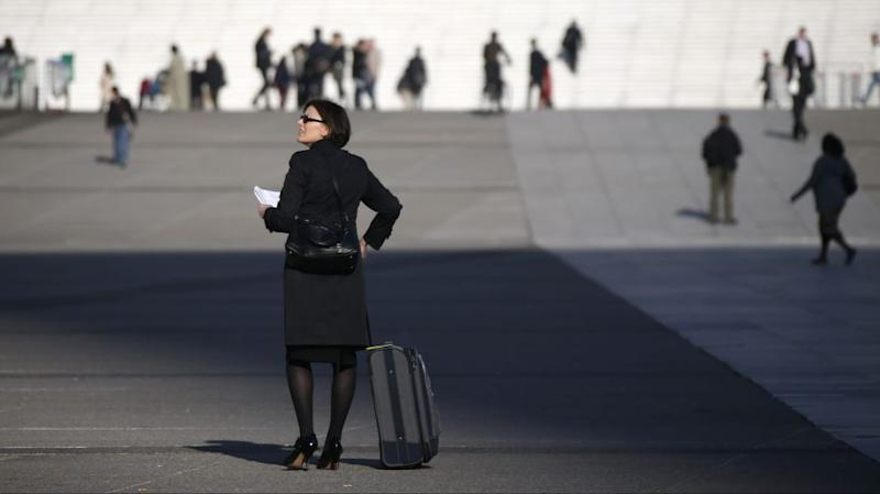 A businesswoman walks on the esplanade of La Defense, in the financial and business district west of Paris