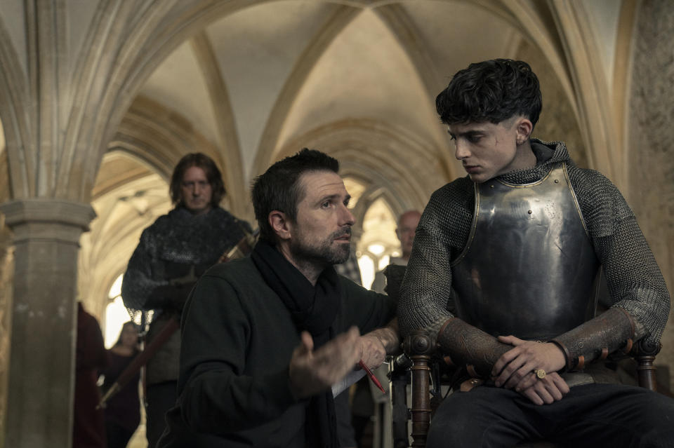 A photo of director David Michod speaking with actor Timotheé Chalamet on set of The King.