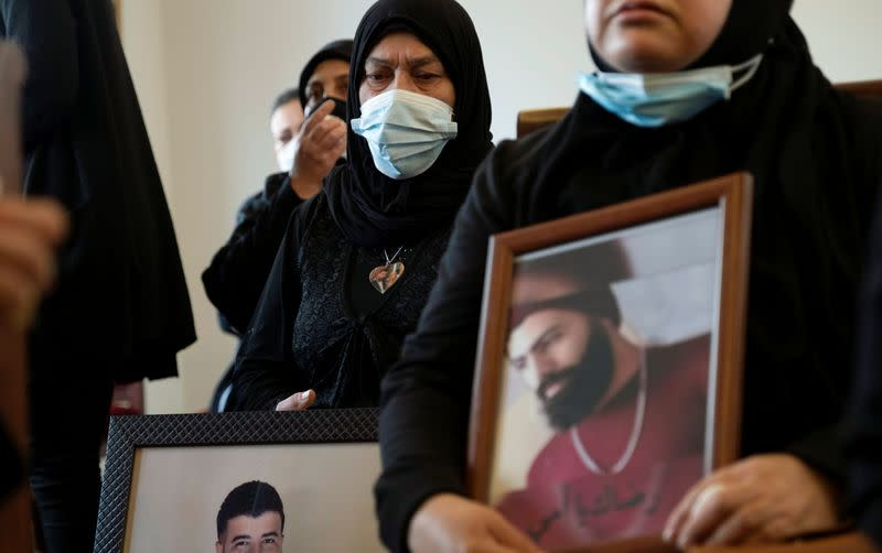 Relatives of victims of Beirut port explosion, hold their pictures during a ceremony in Beirut
