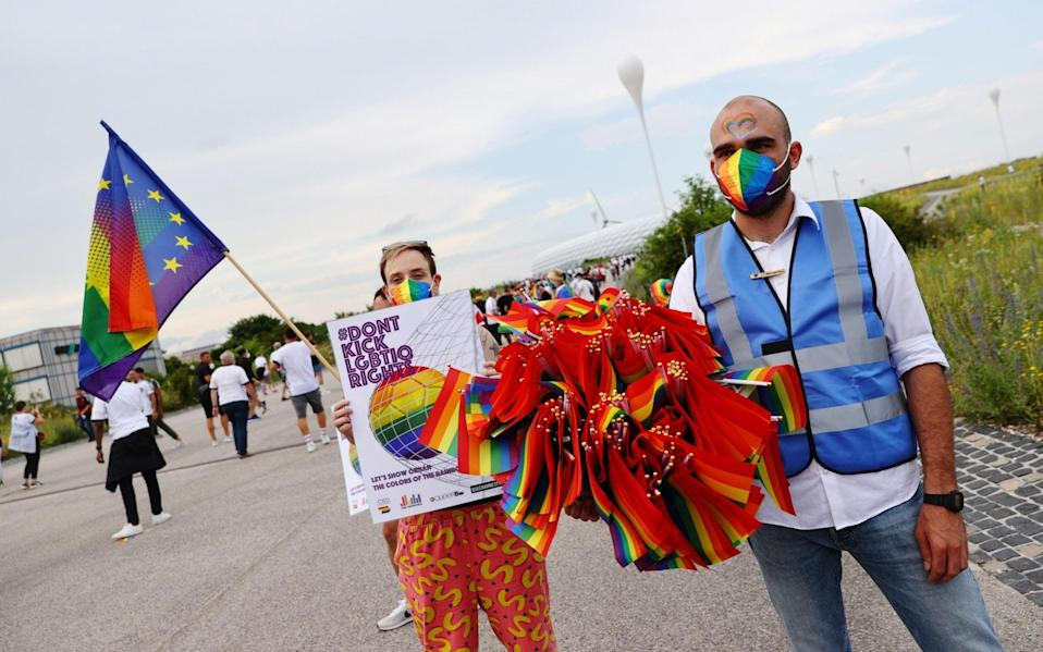 A steward holds rainbow flags outside the stadium - Reuters